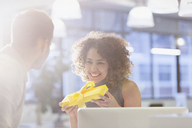 Businesswoman holding gift in office - HOXF00363