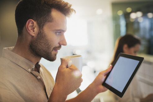 Businessman drinking coffee using digital tablet in office - HOXF00402