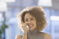 Businesswoman with curly hair talking on telephone - HOXF00414