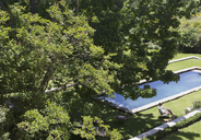 Woman sitting on lawn chair next to sunny swimming pool under green summer trees - HOXF00453