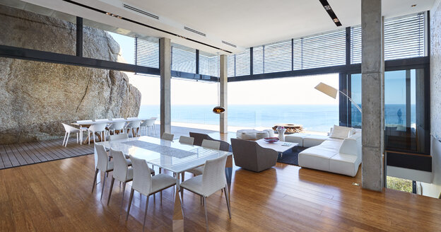 Modern luxury living room and dining room open to patio with ocean view - HOXF00474