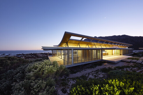 Illuminated modern luxury home showcase exterior with ocean view at dusk - HOXF00498