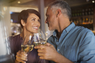 Couple toasting white wine glasses in restaurant - HOXF00510