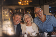 Portrait laughing friends drinking coffee in restaurant - HOXF00516