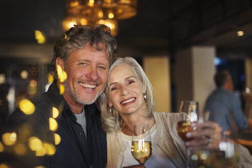 Portrait smiling senior couple toasting white wine glasses in bar - HOXF00528