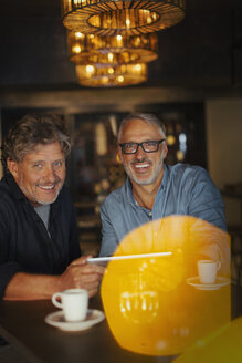 Portrait smiling men using digital tablet and drinking coffee at restaurant table - HOXF00543