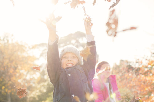 Enthusiastic boy playing in autumn leaves - HOXF00555