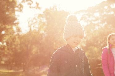 Boy and girl walking among sunny trees - HOXF00558