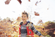 Portrait of enthusiastic boy throwing autumn leaves - HOXF00561