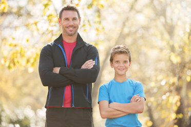 Portrait confident father and son with arms crossed outdoors - HOXF00564