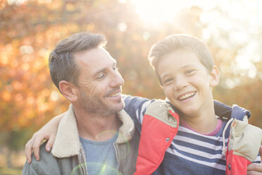 Portrait smiling father and son in front of autumn leaves - HOXF00570