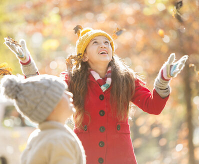 Girl throwing autumn leaves - HOXF00576