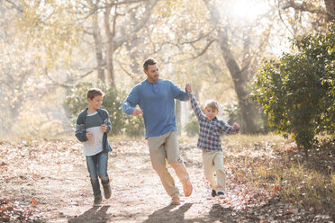 Playful father and sons running on trail in woods - HOXF00585