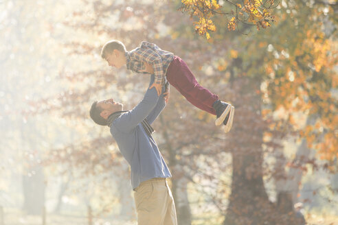 Father lifting son overhead in woods with autumn leaves - HOXF00588