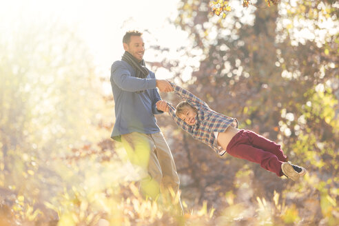 Father spinning son among autumn leaves - HOXF00597