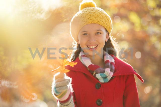 Portrait smiling girl holding golden autumn leaf - HOXF00600 - Tom Merton/Westend61