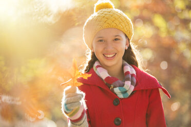 Portrait smiling girl holding golden autumn leaf - HOXF00600