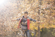 Playful boy playing in autumn leaves - HOXF00621