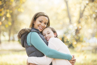 Portrait of smiling mother and daughter hugging outdoors - HOXF00624
