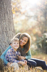Portrait smiling mother and son at tree trunk in autumn woods - HOXF00627