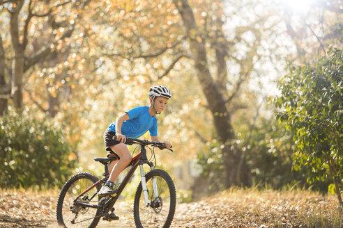 Boy mountain biking on path in woods - HOXF00630