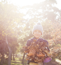 Portrait smiling boy holding bunch of autumn leaves - HOXF00633