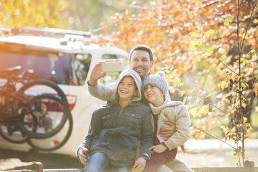 Father and sons taking selfie in autumn park - HOXF00642