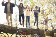 Enthusiastic family jumping from fallen log over bicycles - HOXF00645