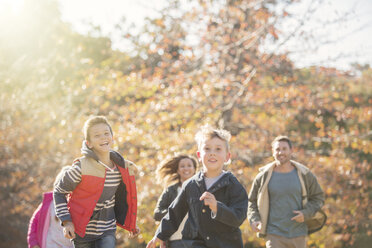 Energetic family running in autumn park - HOXF00648
