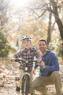 Portrait smiling father teaching son to ride a bike in woods - HOXF00660