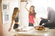 Teenage girls dancing in sunny kitchen - HOXF00693