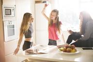 Teenage girls dancing in sunny kitchen - HOXF00693