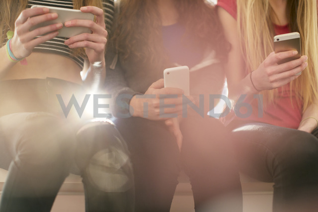 Teenage girls texting with cell phones in a row - HOXF00708