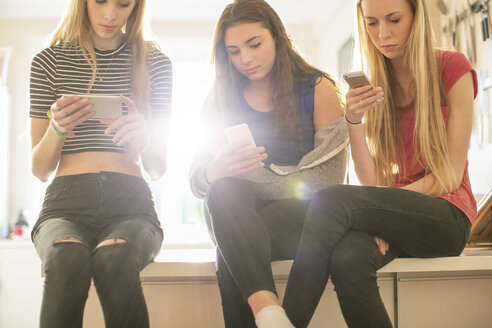 Teenage girls texting with cell phones in kitchen - HOXF00723