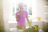 Portrait smiling woman drinking green smoothie in kitchen - HOXF00732
