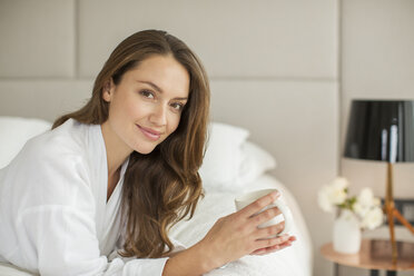 Portrait smiling woman in bathrobe drinking coffee on bed - HOXF00741