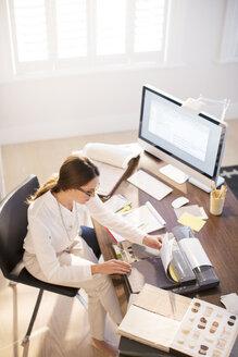 Interior designer examining carpet swatches at desk - HOXF00750