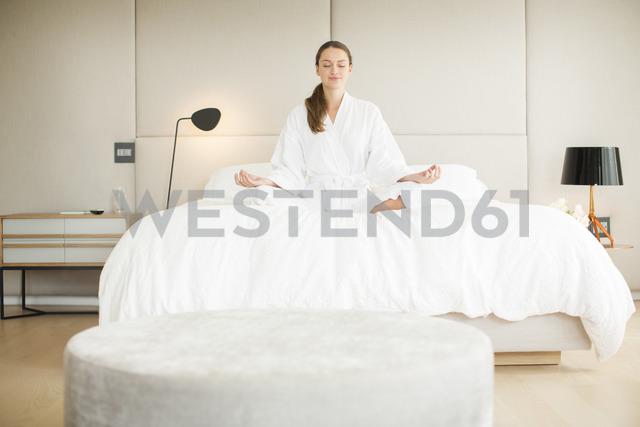 Serene woman in bathrobe meditating in lotus position on bed - HOXF00756 - Tom Merton/Westend61