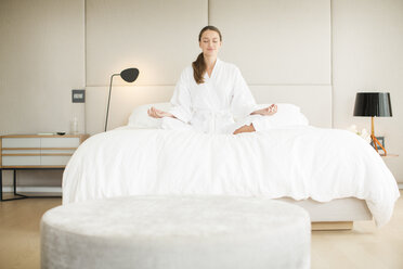 Serene woman in bathrobe meditating in lotus position on bed - HOXF00756