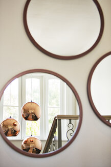 Reflection of copper pendant lights in round mirror - HOXF00771
