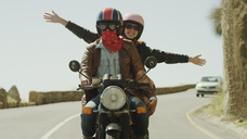 Exuberant young woman riding motorcycle on sunny road - HOXF00786