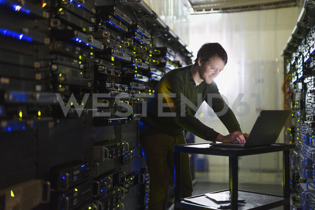 Server room technician working at laptop - HOXF00816