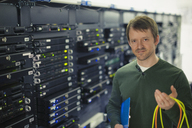 Portrait confident server room technician holding cable - HOXF00855