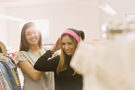 Fashion buyers trying on stocking cap - HOXF00870