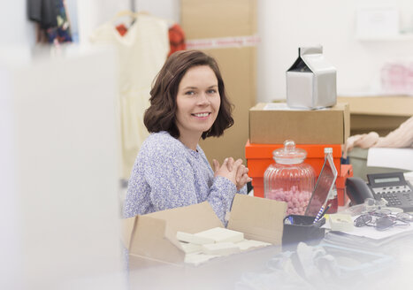 Portrait smiling fashion buyer at messy desk in office - HOXF00879
