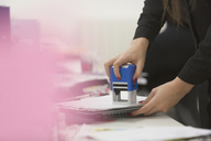 Businesswoman using stamp on paperwork in office - HOXF00891