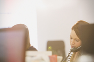 Businesswoman talking on telephone in office - HOXF00894
