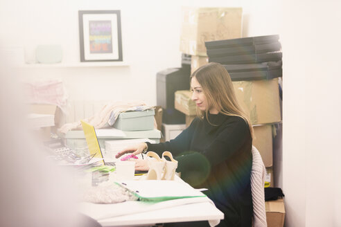 Fashion buyer working at laptop in office - HOXF00906