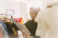 Fashion buyer reviewing paperwork at clothing racks - HOXF00924