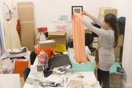 Fashion buyer packaging skirt in messy office - HOXF00927
